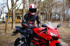 KRASNOYARSK, RUSSIA - May 29, 2018: Beautiful motorcyclist in full gear and helmet on a red and black Honda 2005 CBR 600 RR PC37. KRASNOYARSK, RUSSIA - May 29 stock photos