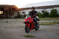 KRASNOYARSK, RUSSIA - May 29, 2018: Beautiful motorcyclist in full gear and helmet on a red and black Honda 2005 CBR 600 RR PC37. KRASNOYARSK, RUSSIA - May 29 stock photo