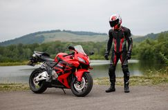 KRASNOYARSK, RUSSIA - May 29, 2018: Beautiful motorcyclist in full gear and helmet on a red and black Honda 2005 CBR 600 RR PC37. KRASNOYARSK, RUSSIA - May 29 royalty free stock photography