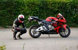 KRASNOYARSK, RUSSIA - May 29, 2018: Beautiful motorcyclist in full gear and helmet on a red and black Honda 2005 CBR 600 RR PC37. KRASNOYARSK, RUSSIA - May 29 stock images