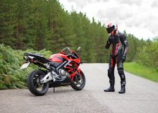 KRASNOYARSK, RUSSIA - May 24, 2018: Beautiful motorcyclist in full gear and helmet on a red and black Honda 2005 CBR 600 RR PC37 royalty free stock image