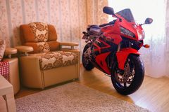 KRASNOYARSK, RUSSIA - SEPTEMBER 9, 2017: Red and black sportbike Honda CBR 600 RR 2005 PC37 in house. The motorcycle in the apart royalty free stock image