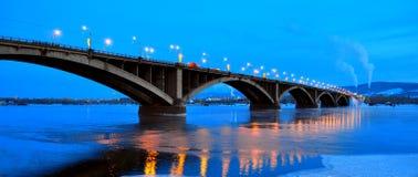 Krasnoyarsk Ryssland - Januari 2017 aftonsikt av den kollektiva bron över Yeniseiet River med reflexion i vattnet buna arkivfoto