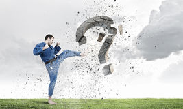 Krate man in action. Karate man in jump breaking question mark Royalty Free Stock Images