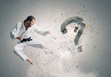Krate man in action. Karate man in jump breaking question mark Stock Photos