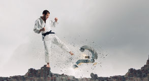 Krate man in action. Karate man in jump breaking question mark Stock Photography