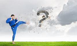 Krate man in action. Karate man in jump breaking question mark Royalty Free Stock Photo