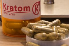 Kratom pills on a desk. Image of actual kratom pills with a faux prescription logo Royalty Free Stock Photography