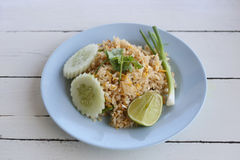 Kratzen Sie Fried Rice von thailändischen Nahrungsmitteln im blauen Teller Stockfotografie