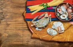 Kratzen Sie, Meeresfrüchte mit Spaghettis und Oberteile auf ethnischem Gewebe und hölzernem Brett Stockfotos