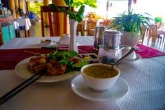 Kratzen Sie Suppe, gebratene Frühlingsrollen mit Garnele und vietnamesischen Kaffee im Küstencafé Stockfoto