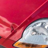 Kratzer und rostige Einbuchtung auf Front des roten Autos lizenzfreies stockbild