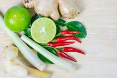 Kraut und würzige Bestandteile für die Herstellung des thailändischen Lebensmittels auf hölzernem Hintergrund Lizenzfreie Stockbilder