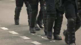 Kravallpolis som går på vägen stock video
