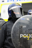 Kravallpolistjänsteman med skölden och hjälmen Royaltyfria Foton