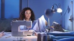 Krawiecka jest ubranym błękitna bluzka i mieć elastycznej władcy na ona ramiona pracuje przy atelier zdjęcie wideo