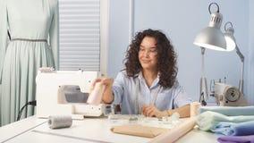 Krawiecka jest ubranym błękitna bluzka i mieć elastycznej władcy na ona ramiona pracuje przy atelier zbiory wideo