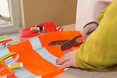 Krawiecka kobieta, projektant mody pracuje przy studiiem Projektant mody tnąca tkanina obok szwalnej maszyny Zdjęcie Stock