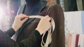 Krawieckie bierze miary z pomiarową taśmą na nowej brąz kurtce zbiory wideo