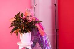 Kreative ältere Frauenstellung nah an Anlage lizenzfreie stockfotografie