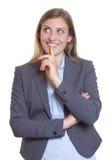 Kreative blonde Geschäftsfrau in einem grauen Blazer Lizenzfreie Stockfotografie