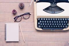 Kreative Ebenenlage des Weinlesearbeitsplatzschreibtisches mit Schreibmaschine, Gläsern und Notizbuch, hölzerne Beschaffenheit Lizenzfreie Stockfotos