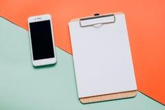 Kreative Ebenenlage von Smartphone und von leerem Klemmbrett Lizenzfreie Stockbilder
