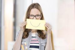 Kreative Geschäftsfrau, die Papier mit Lächeln gezeichnet auf es hält stockfotos