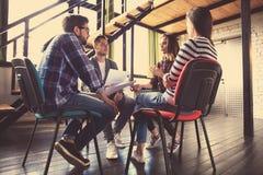 Kreative Geschäftsleute, die im Kreis von Stühlen sich treffen Lizenzfreies Stockfoto
