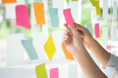 Kreative Geschäftsleute, die klebrige Anmerkungen auf Glaswand mit lesen Lizenzfreies Stockfoto