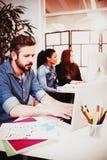 Kreative Geschäftsleute, die Technologien am Schreibtisch einsetzen lizenzfreies stockfoto