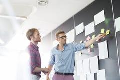 Kreative Geschäftsmänner, die über klebrigem Papier auf Wand im Büro sich besprechen Lizenzfreies Stockbild