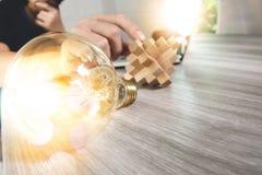 kreative Hand, die hölzernes Puzzlespiel und Glühlampe mit Laptop-COM zeigt Lizenzfreies Stockfoto