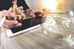 kreative Hand, die hölzernes Puzzlespiel und Glühlampe mit Laptop-COM zeigt Lizenzfreie Stockfotos