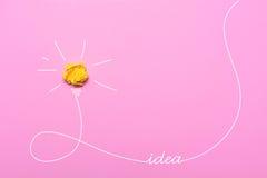 Kreative Idee des zerknitterten Papiers Eine brennende Glühlampe auf einem rosa Hintergrund Stockbilder
