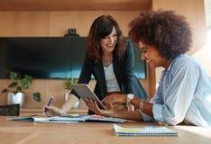Kreative weibliche Führungskräfte, die digitale Tablette im Büro verwenden Lizenzfreie Stockbilder