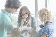Kreative Wirtschaftler, die Farbmuster im Büro analysieren Lizenzfreie Stockfotografie
