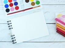 Kreativer Arbeitsplatz mit gewundenem Notizbuch, Acrylfarbensatz und Pastellen Lizenzfreie Stockfotografie