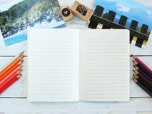 Kreativer Arbeitsplatz mit gezeichnetem offenem Notizbuch, Postkarten, färbte Bleistifte und Stempel Lizenzfreie Stockbilder