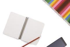 Kreativer Arbeitsplatzschreibtisch mit Notizbuch, Smartphone und Bleistiften auf weißem Hintergrund Stockfoto