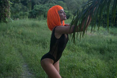 Kreativer Blick der sexy Frau in der orange Perücke lokalisiert im Palmewald Stockfoto