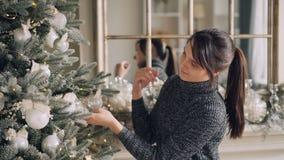Kreativer Brunette verziert den Weihnachtsbaum, der schöne Bälle berühren und die Beleuchtung, die zur Partei fertig wird stock video footage