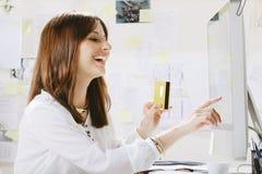 Kreativer Designer der jungen Frau, der Zahlungen on-line leistet. Lizenzfreie Stockfotos