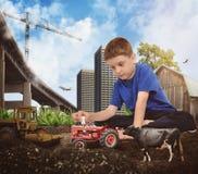 Kreativer Gebäude-Junge, der mit Ackerschlepper spielt Stockfoto