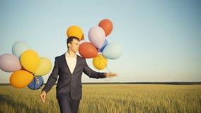 Kreativer Geschäftsmannweg an einem Feld, das bunte Ballone hält stock video