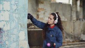 Kreativer Graffitimaler der jungen Frau benutzt Farbenspray, um ruinierte Säule innerhalb des alten leeren Lagers zu verzieren Mä stock footage