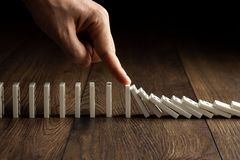 Kreativer Hintergrund, die Hand der Männer stoppte Domino-Effekt, auf einem braunen hölzernen Hintergrund Konzept des Dominoeffek stockfoto