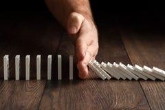 Kreativer Hintergrund, die Hand der M?nner stoppte Domino-Effekt, auf einem braunen h?lzernen Hintergrund Konzept des Dominoeffek stockbilder