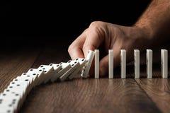 Kreativer Hintergrund, die Hand der M?nner stoppte Domino-Effekt, auf einem braunen h?lzernen Hintergrund Konzept des Dominoeffek stockfotografie