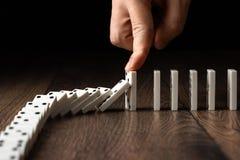 Kreativer Hintergrund, die Hand der M?nner stoppte Domino-Effekt, auf einem braunen h?lzernen Hintergrund Konzept des Dominoeffek lizenzfreies stockfoto